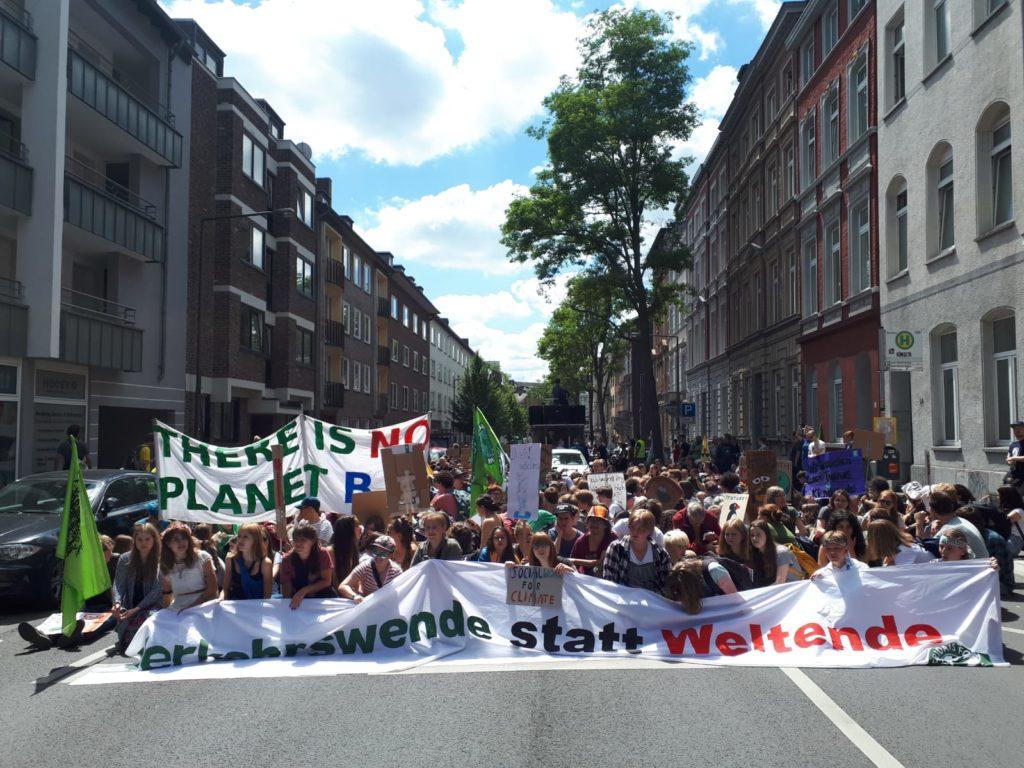 """Banner """"Verkehrsende statt Weltende"""", Sitzende Demonstranten"""