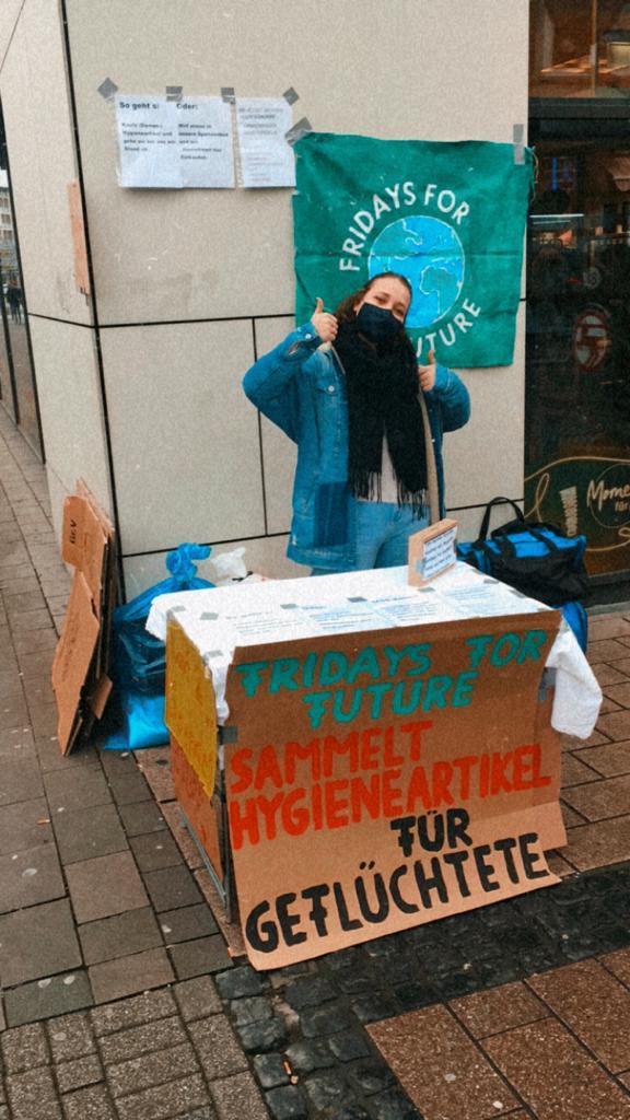 """Aktivistin hinter Tisch mit Plakat mit Aufschrift """"Fridays For Future sammelt Hygieneartikel für Geflüchtete"""""""