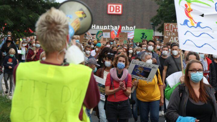 Person mit Warnweste und Megafon im Vordergrund. Im Hintergrund viele Menschen mit Demoschilder. Dahinter Gebäude mit Aufschrift 'Hauptbahnhof'.